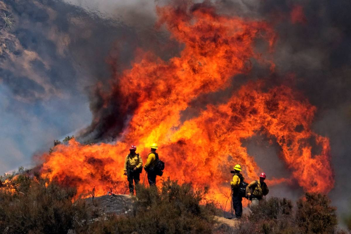 Firefighters watch the Apple Fire in Banning, Calif., Sunday, Aug. 2, 2020. (AP Photo/Ringo H.W ...