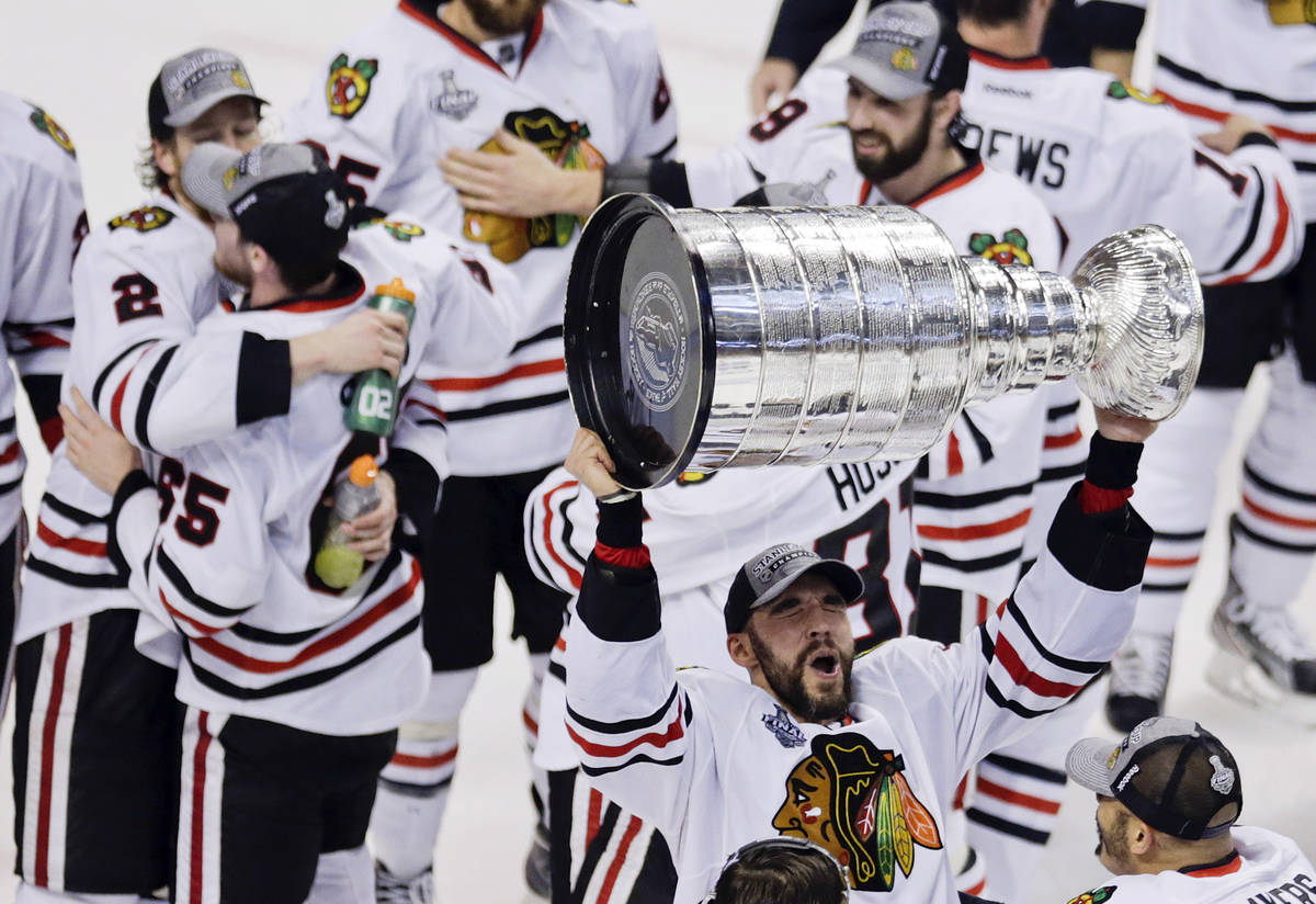 In this June 24, 2013, file photo, Chicago Blackhawks defenseman Michal Rozsival hoists the Sta ...