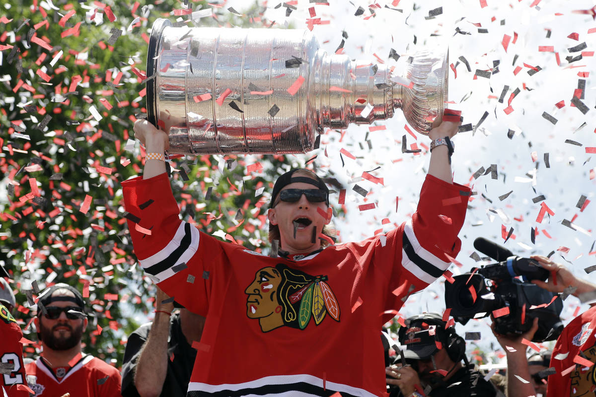 Chicago Blackhawks right wing Patrick Kane (88) holds up the Stanley Cup Trophy during a rally ...