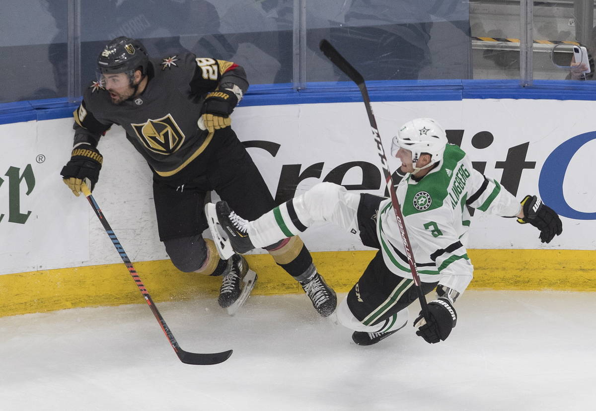 Dallas Stars' John Klingberg (3) is checked by Vegas Golden Knights' William Carrier (28) durin ...