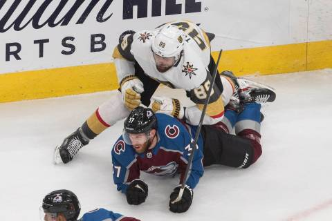 Colorado Avalanche's J.T. Compher (37) is checked by Vegas Golden Knights' Alex Tuch (89) durin ...