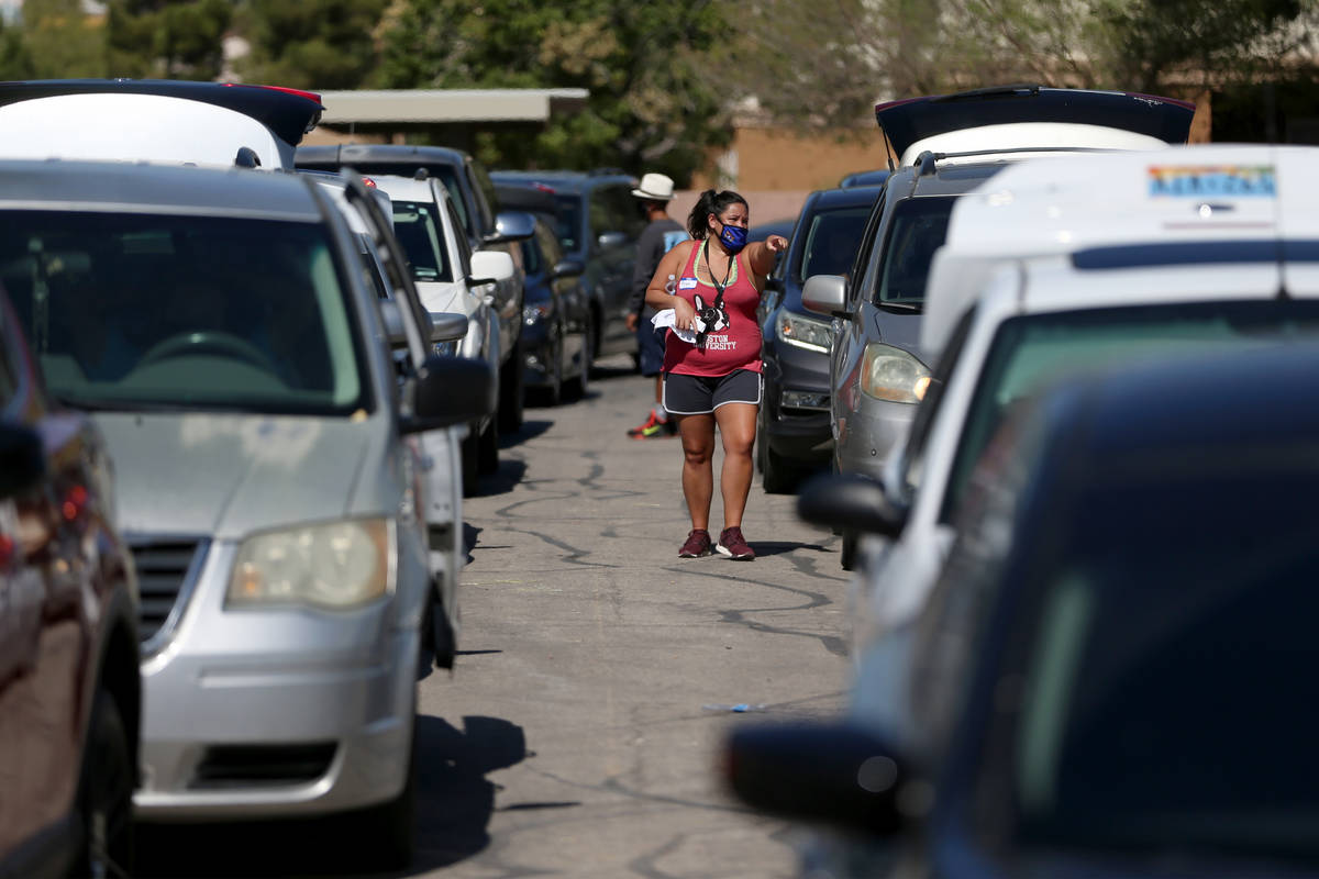 Cars line up during the C-U-R-E Drive Through Resource Fair at Mater Academy in east Las Vegas, ...