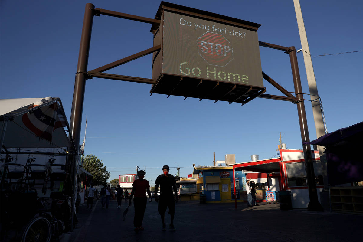 A digital sign reminds people to go home when sick at Broadacres Marketplace in North Las Vegas ...