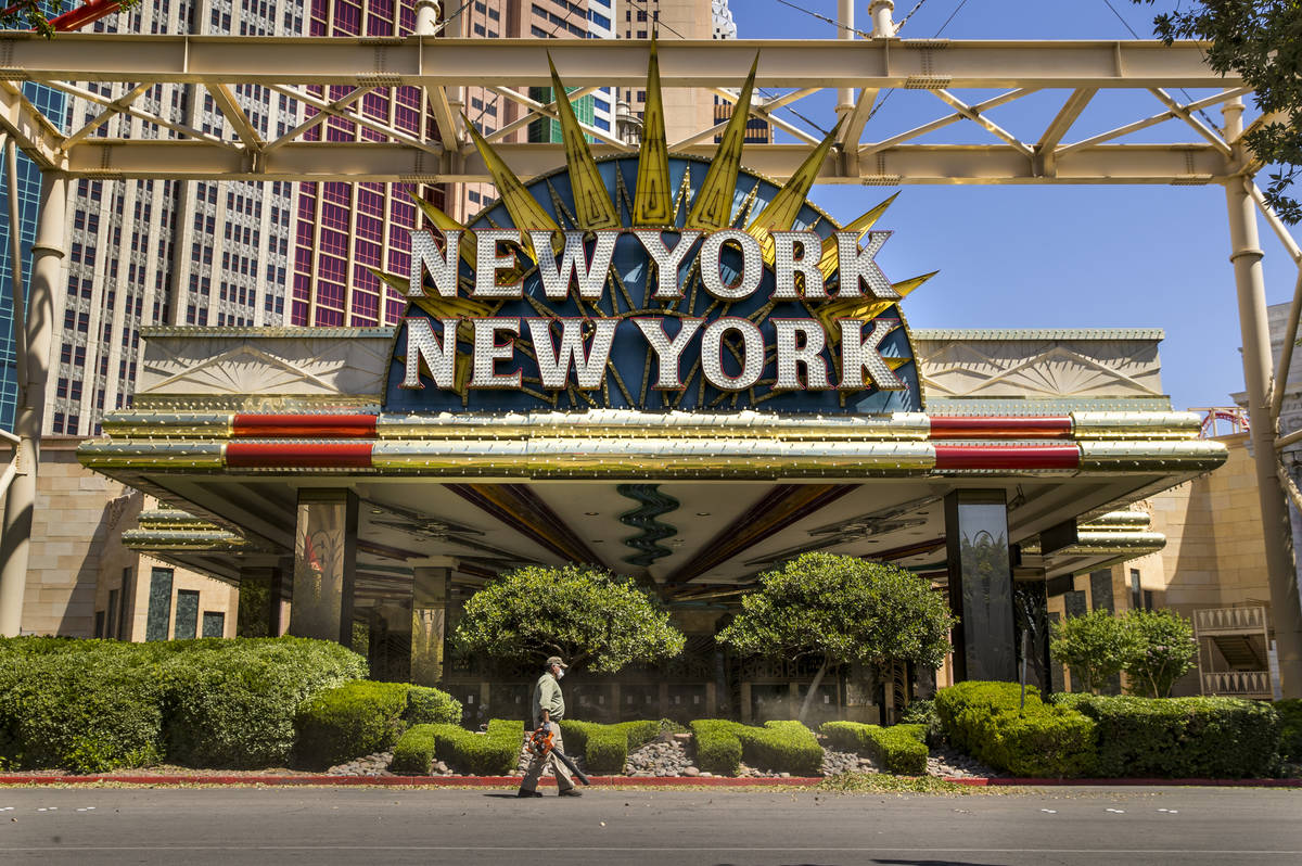 A landscaper blows clippings after trimming the bushes in front of New York-New York on the Las ...