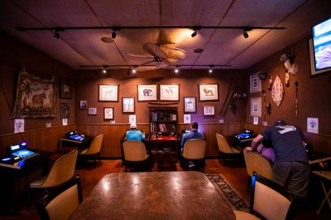 People play on gaming machines that were formerly at the bar in a lounge area at Black Mountain ...