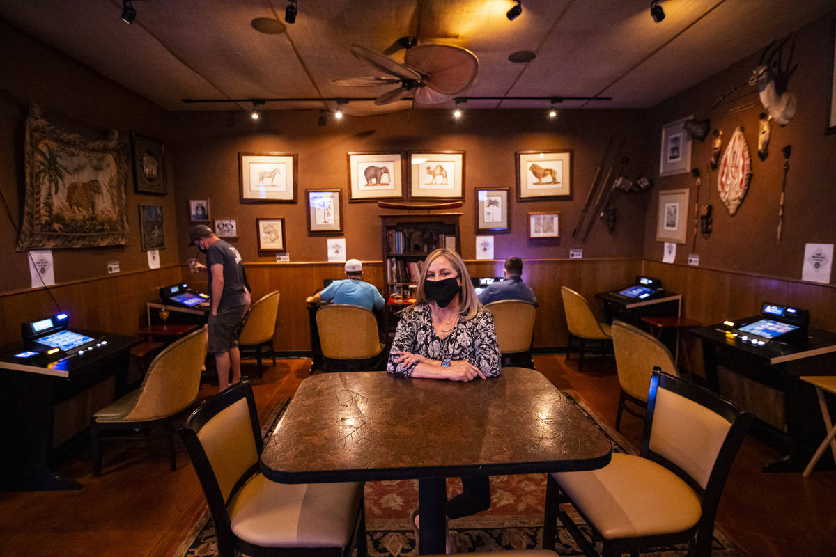 Donna Rocker, owner of Black Mountain Grill, poses by a gaming lounge area at the restaurant an ...
