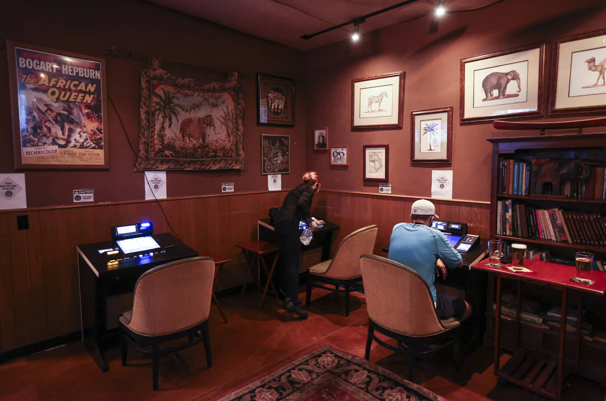 Bartender Silken Widmer sanitizes a gaming device in a lounge area at Black Mountain Grill in H ...