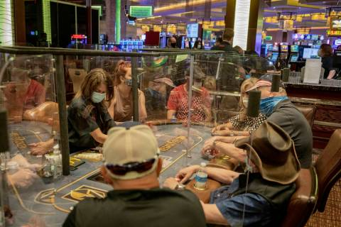 Individuals play eight-handed poker games using plexiglass dividers between the players in the ...