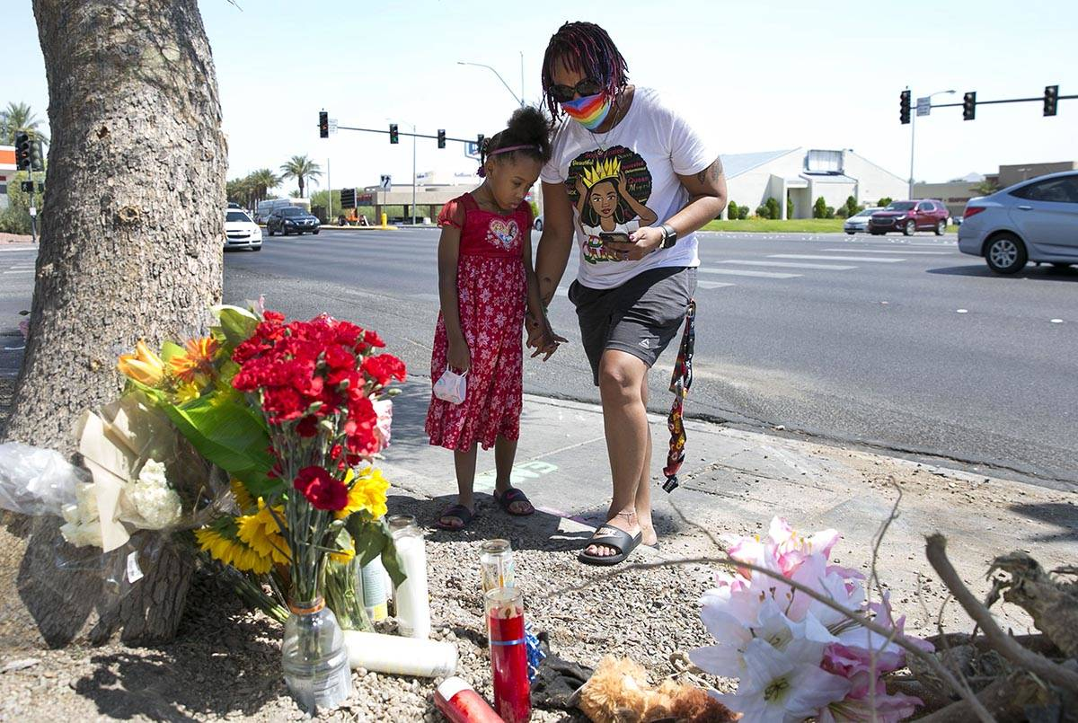 Tiffany Joseph and her daughter Jordan, 6, visit a makeshift roadside memorial on Wednesday, Au ...