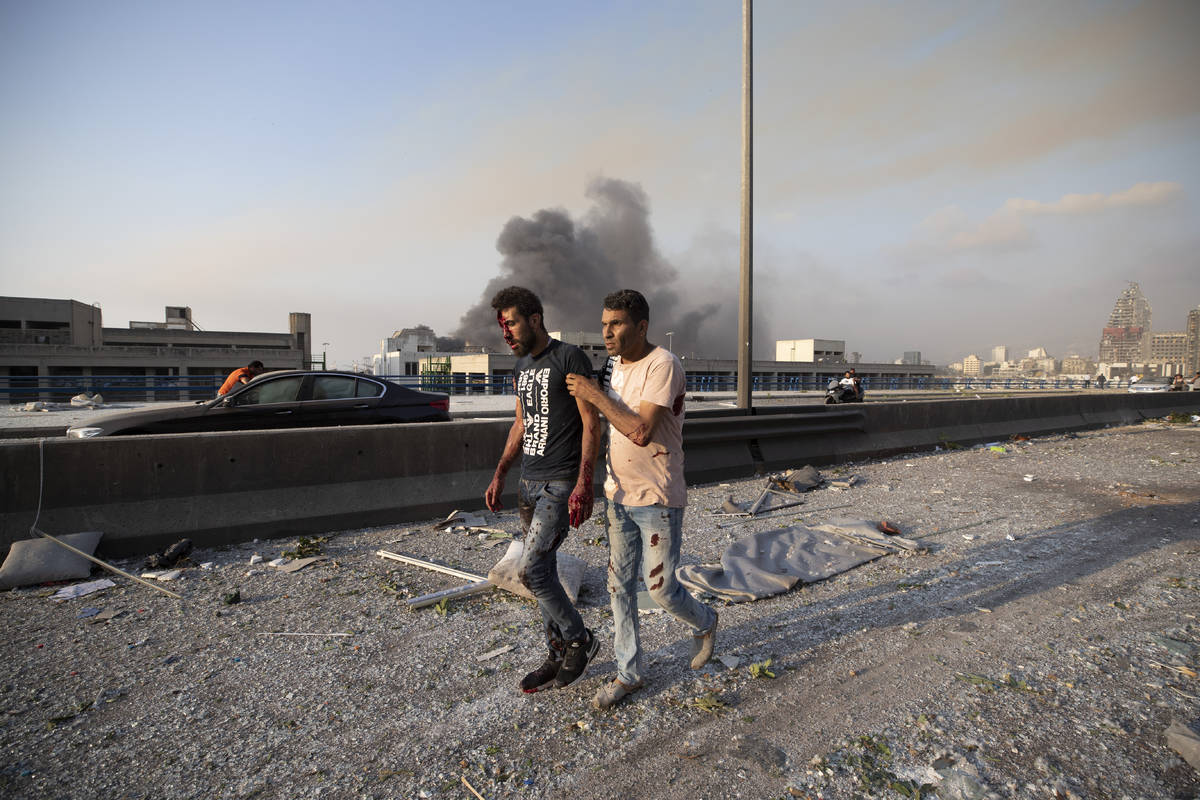 A man wounded in a massive explosion is led away in Beirut, Lebanon, Tuesday, Aug. 4, 2020. Mas ...