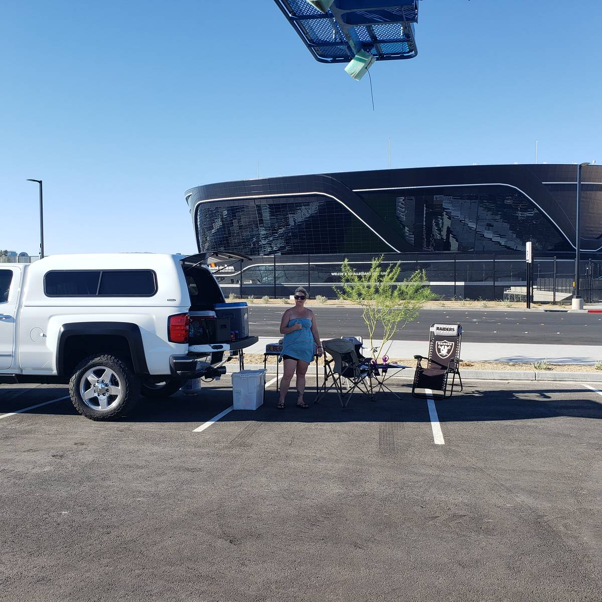 Tonie Silva stand with her tailgate spread with the recently completed Allegiant Stadium in the ...