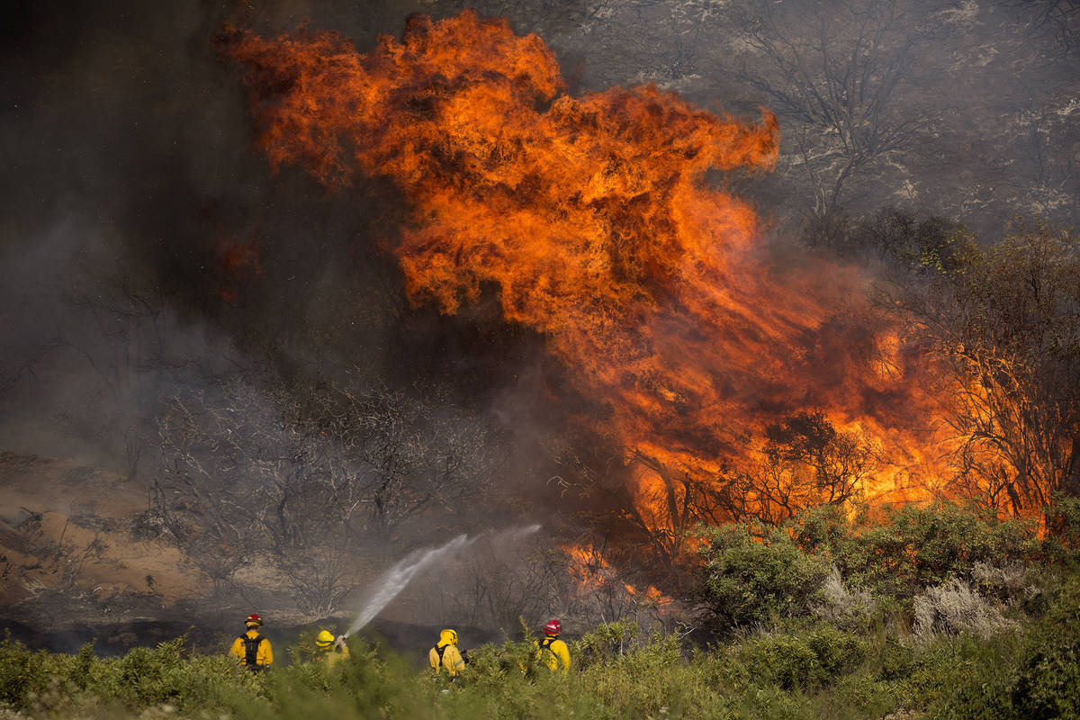Firefighters work against the Apple Fire near Banning, Calif., on Sunday, Aug. 2, 2020. Smoke f ...