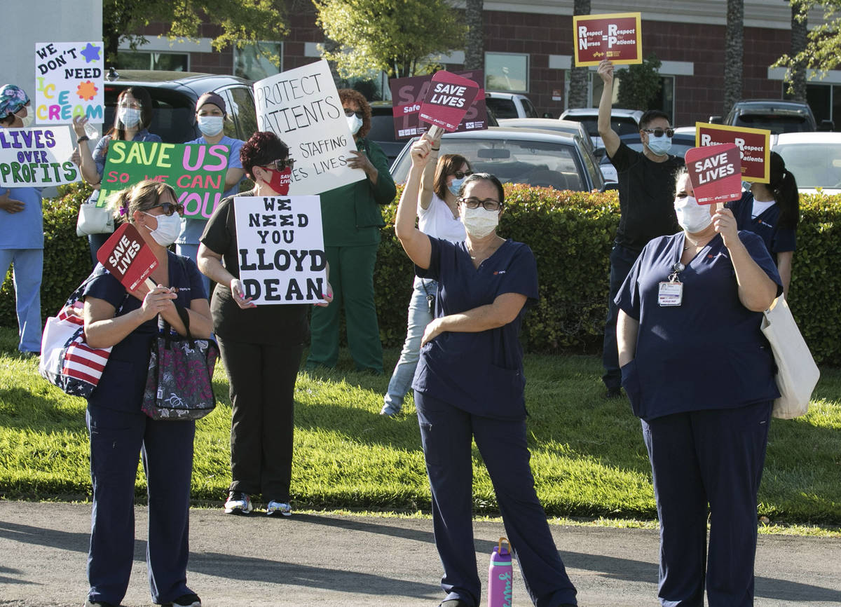 Registered Nurses Zully Hernandez, center and Aariana Kovacs, right, picket outside of St. Rose ...