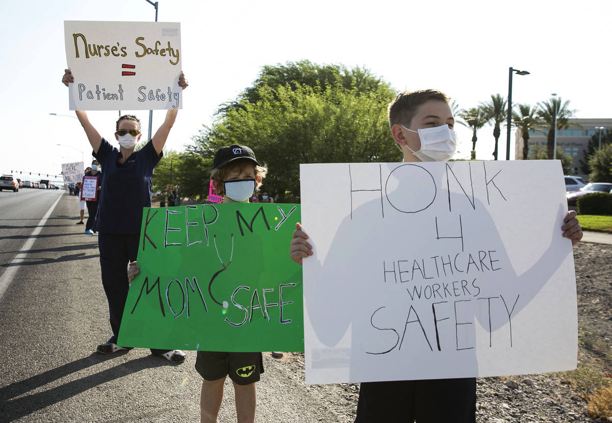 Oliver Smith, 10, right, his brother Elliot, 6, picket with their mother Registered Nurse, Ande ...
