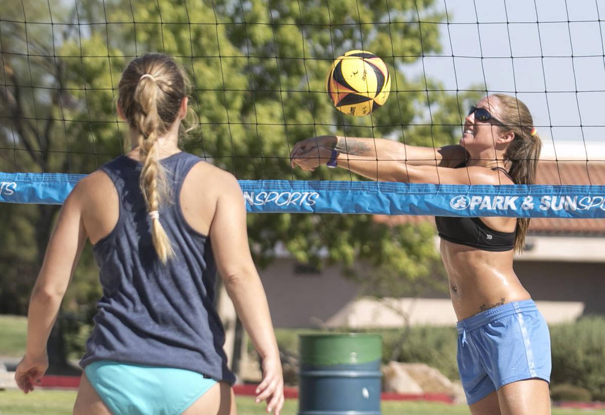 Lindsay Hostetler returns the ball as Elisabeth Rice, left, looks on as they play beach volleyb ...