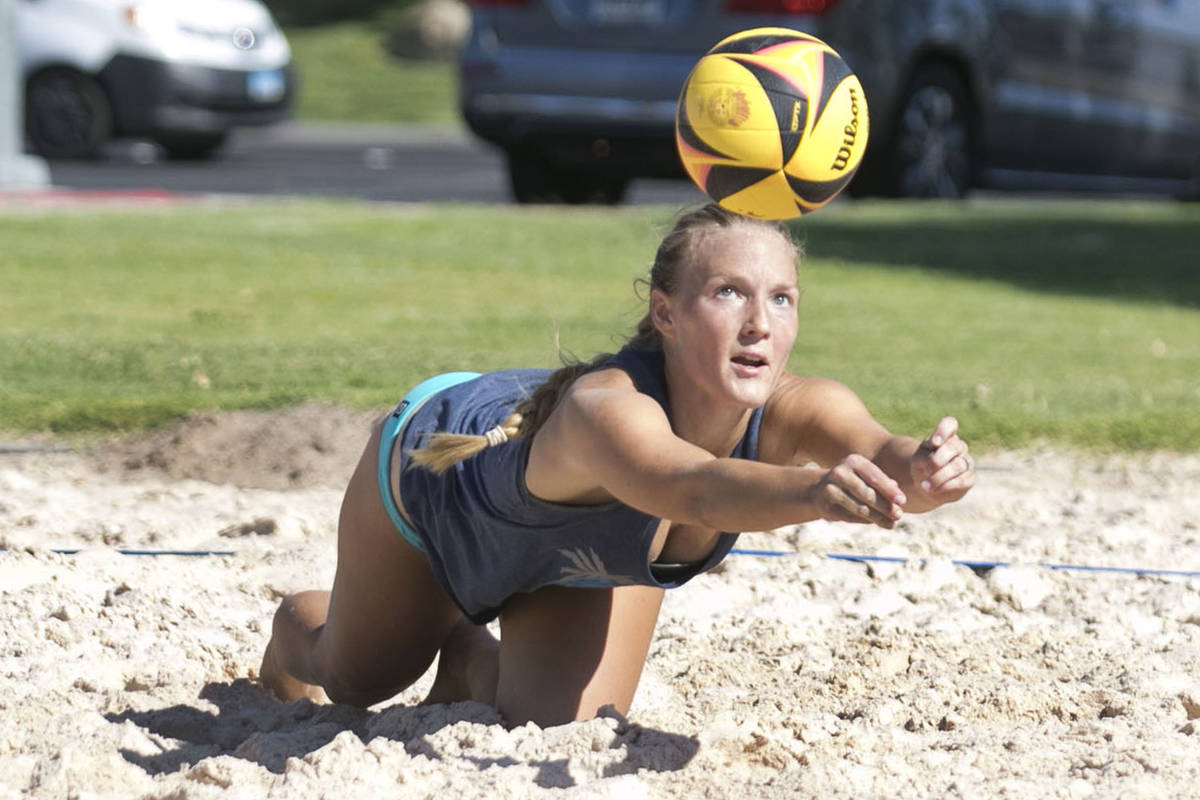Elisabeth Rice dives for the ball as she plays beach volleyball early morning to beat the heat ...