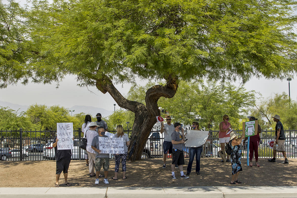 Gig workers gather with signs along E. Washington Ave. to protest the Nevada unemployment offic ...