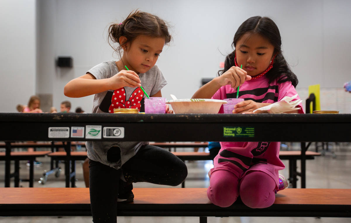 Kylie, 5, left, and Teagan, 5, play with paint in the cafeteria during a summer camp at Legacy ...