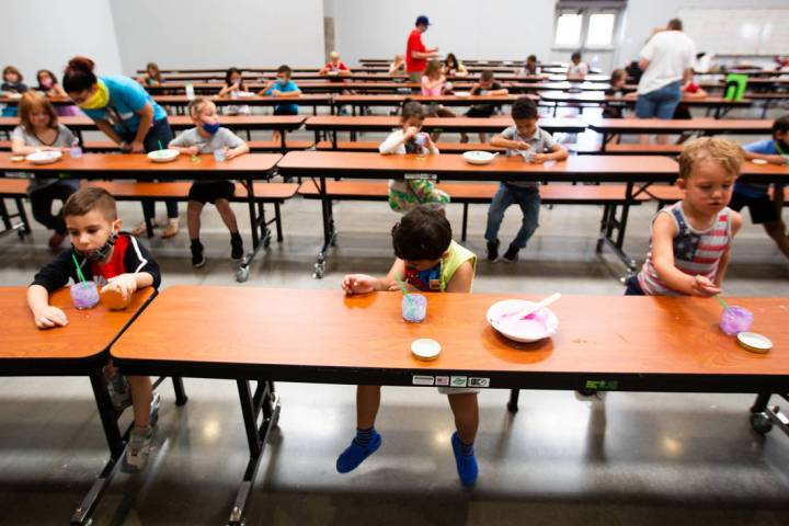 Children play with paint in the cafeteria during a summer camp at Legacy Traditional School in ...