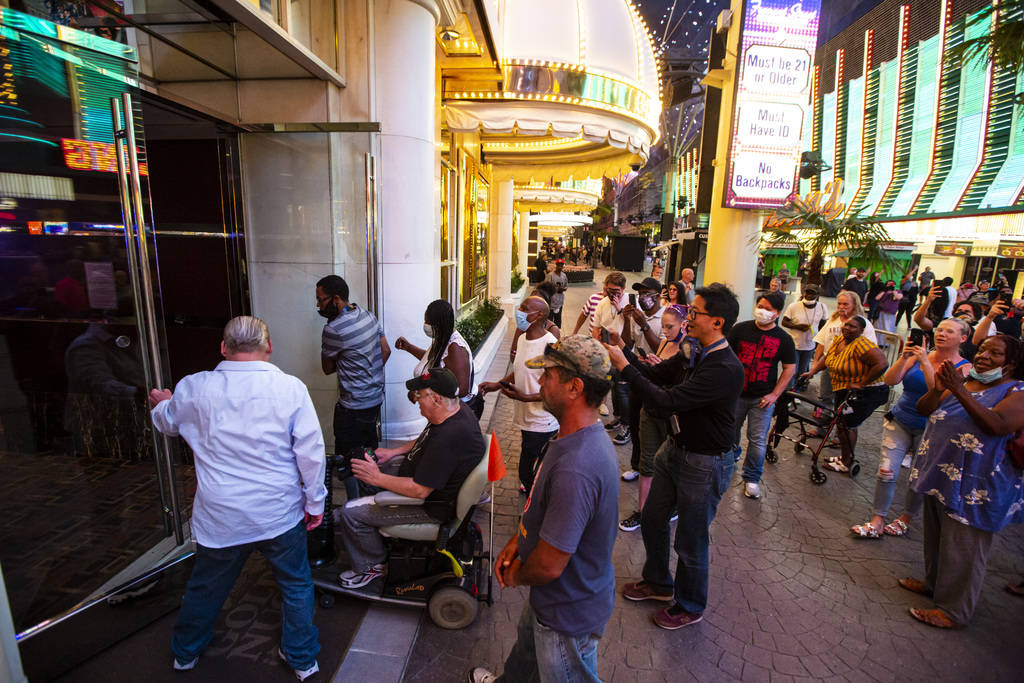 People enter the Golden Nugget at 12:01 a.m. as hotel-casinos reopen in downtown Las Vegas on T ...