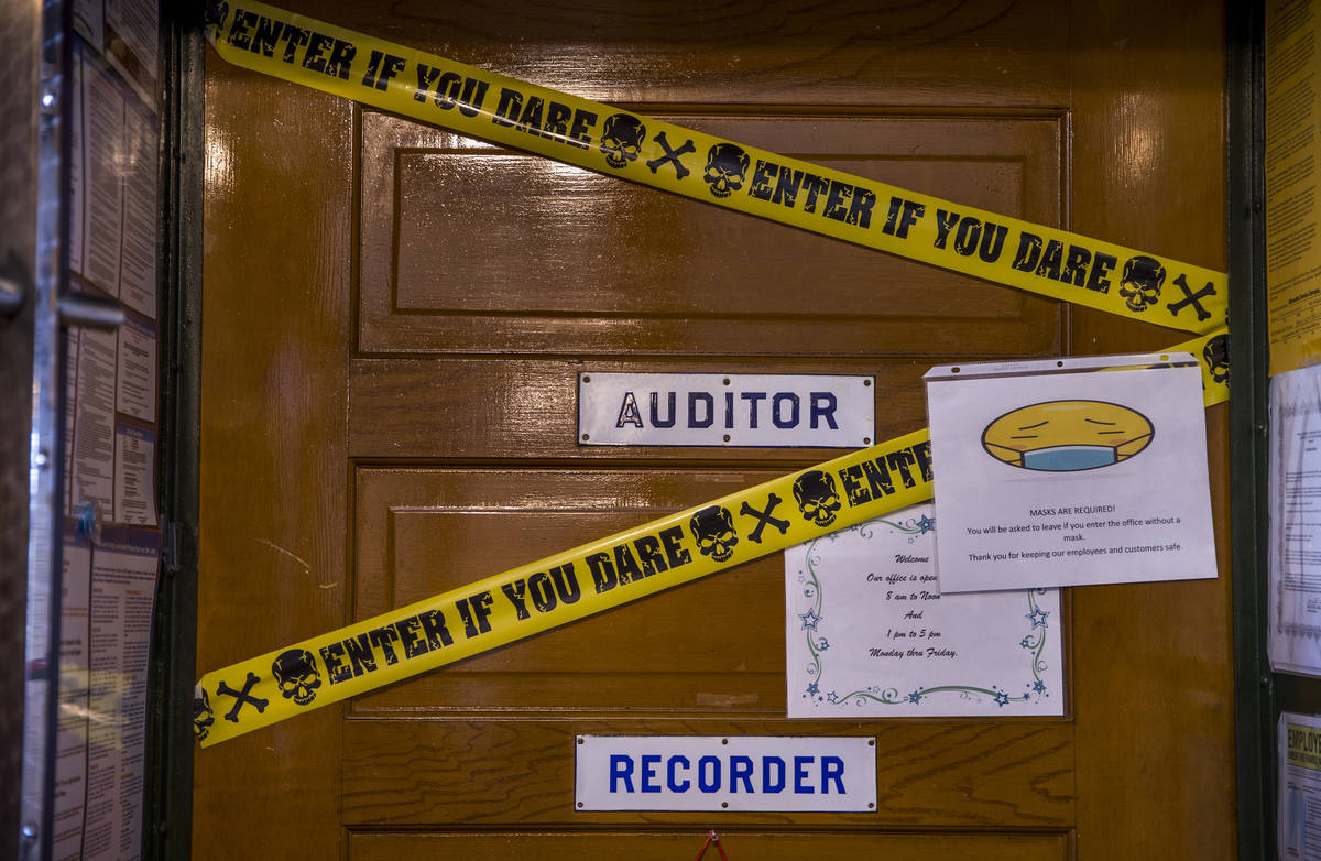 A face covering sign and a little humor mark the Auditor and Recorder office door within the Es ...