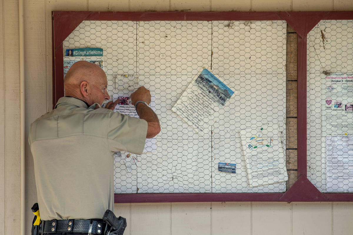 Sheriff's Deputy Ken Aldrich hangs a new COVID-19 drive-thru testing notice at the Esmeralda Ma ...