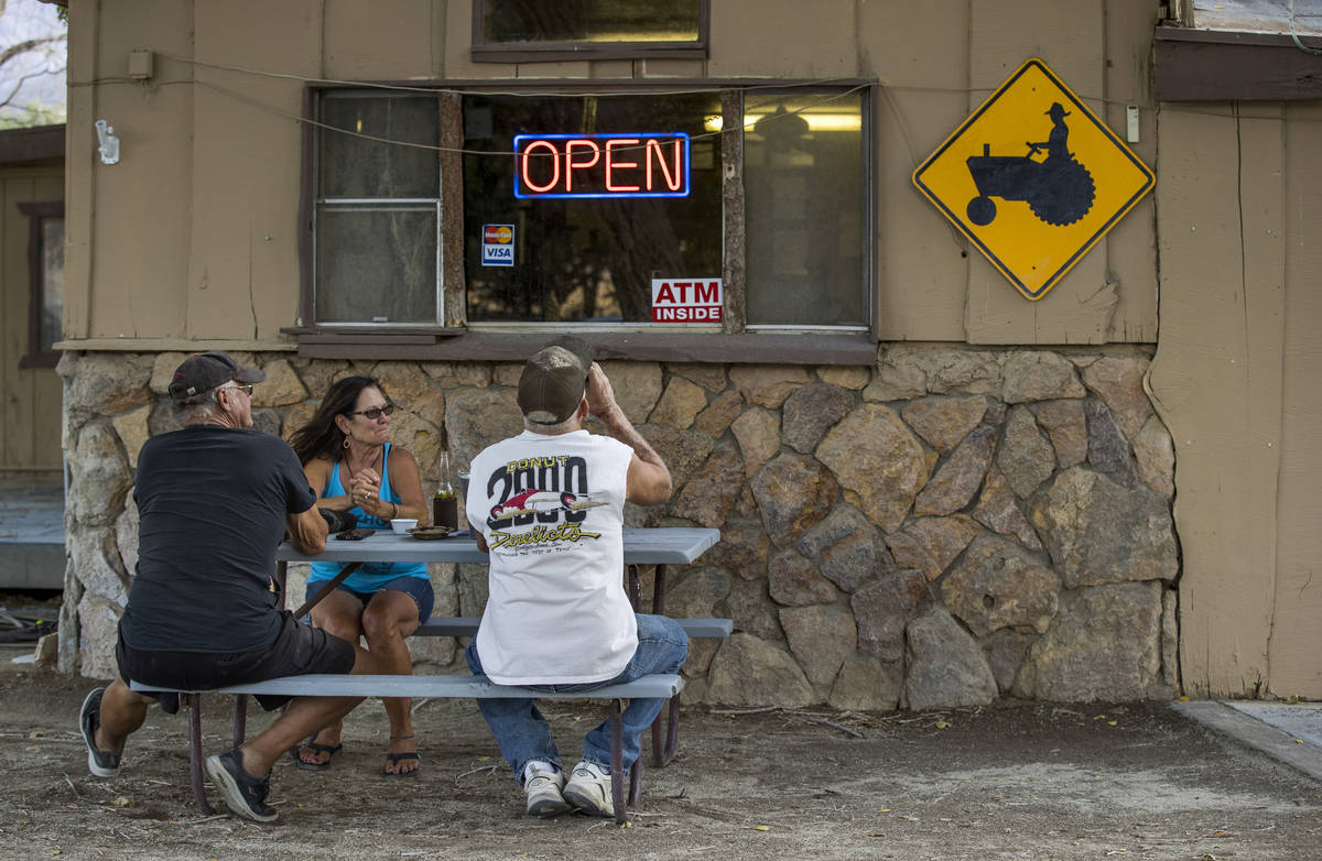 (From left) Hugh and Deb Burton join friend Kevin Goss for a drink while outside of The Boonies ...