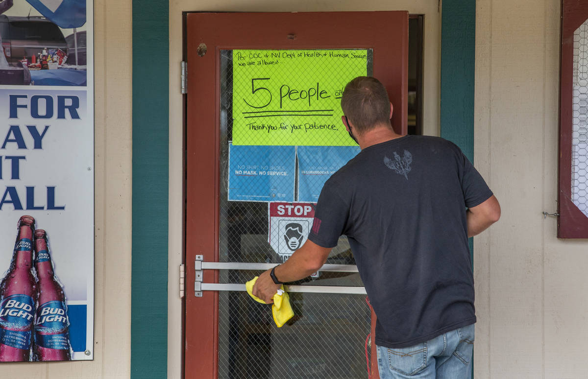 Jim Pringle wipes down the front door at the Esmeralda Market which enforces a face covering po ...