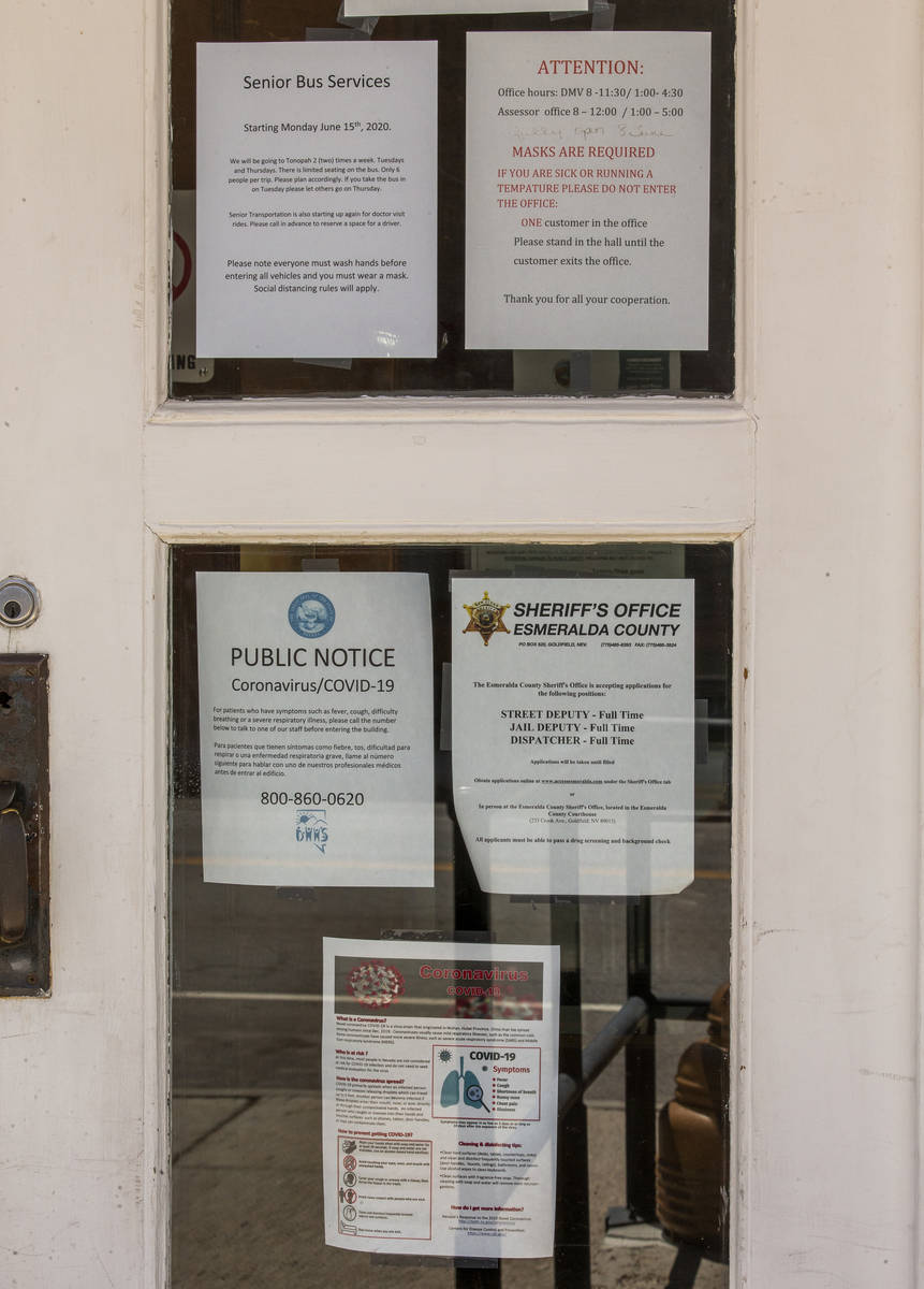 Numerous COVID-19 notices are taped to the front windows at the Esmeralda County Courthouse on ...