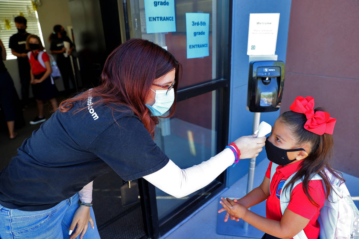 Lianna Garcia rubs her hands with sanitizer as she gets her temperature taken by Vanessa Sanche ...