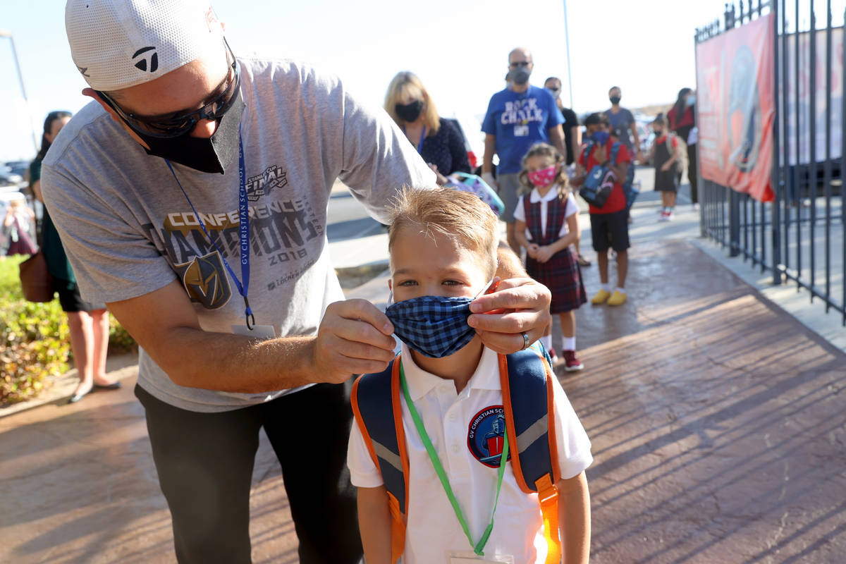 Kindergartner Dominic Martin, 6, gets his mask adjusted by his father Jason Martin on the first ...
