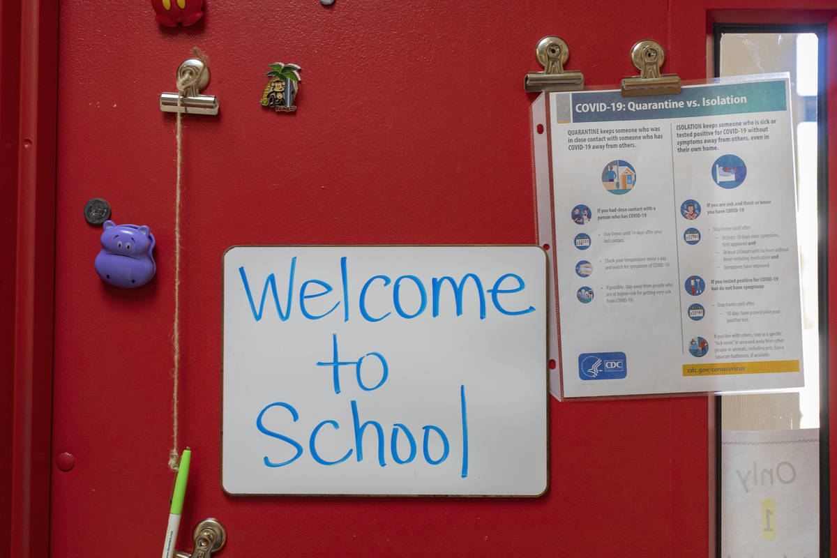 A sign welcoming students to school next to a COVID-19 guide is seen in a classroom on the firs ...