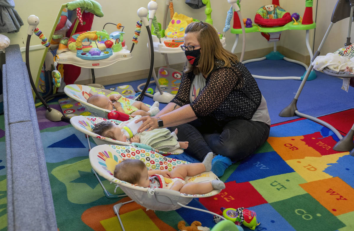 Ms. Marilyn Leyson feeds an infant in the newborn room during the first day of school at Shenke ...