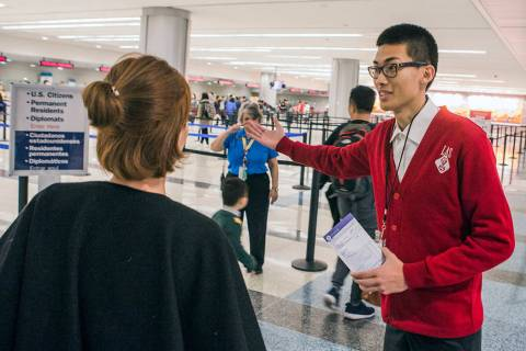 Shingling Guo, right, a Malarian-speaking ambassador, assists a passenger from Hainan Airline f ...