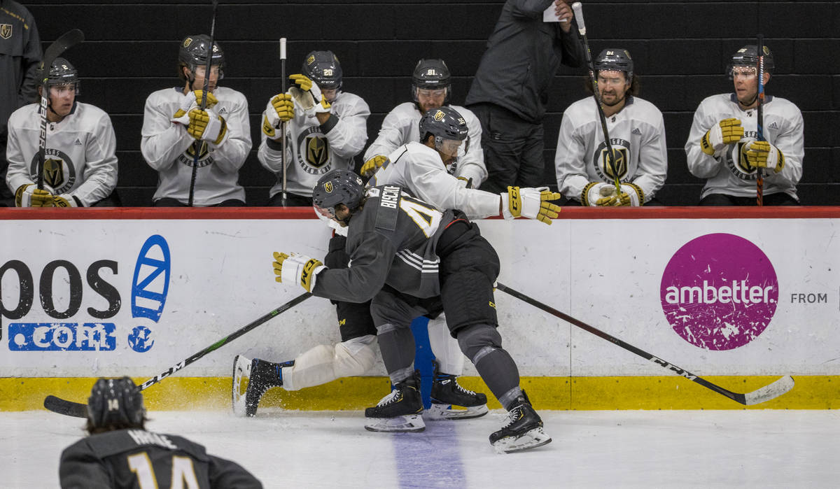 Vegas Golden Knights defenseman Jake Bischoff (45, left) puts a hard check on right wing Keegan ...