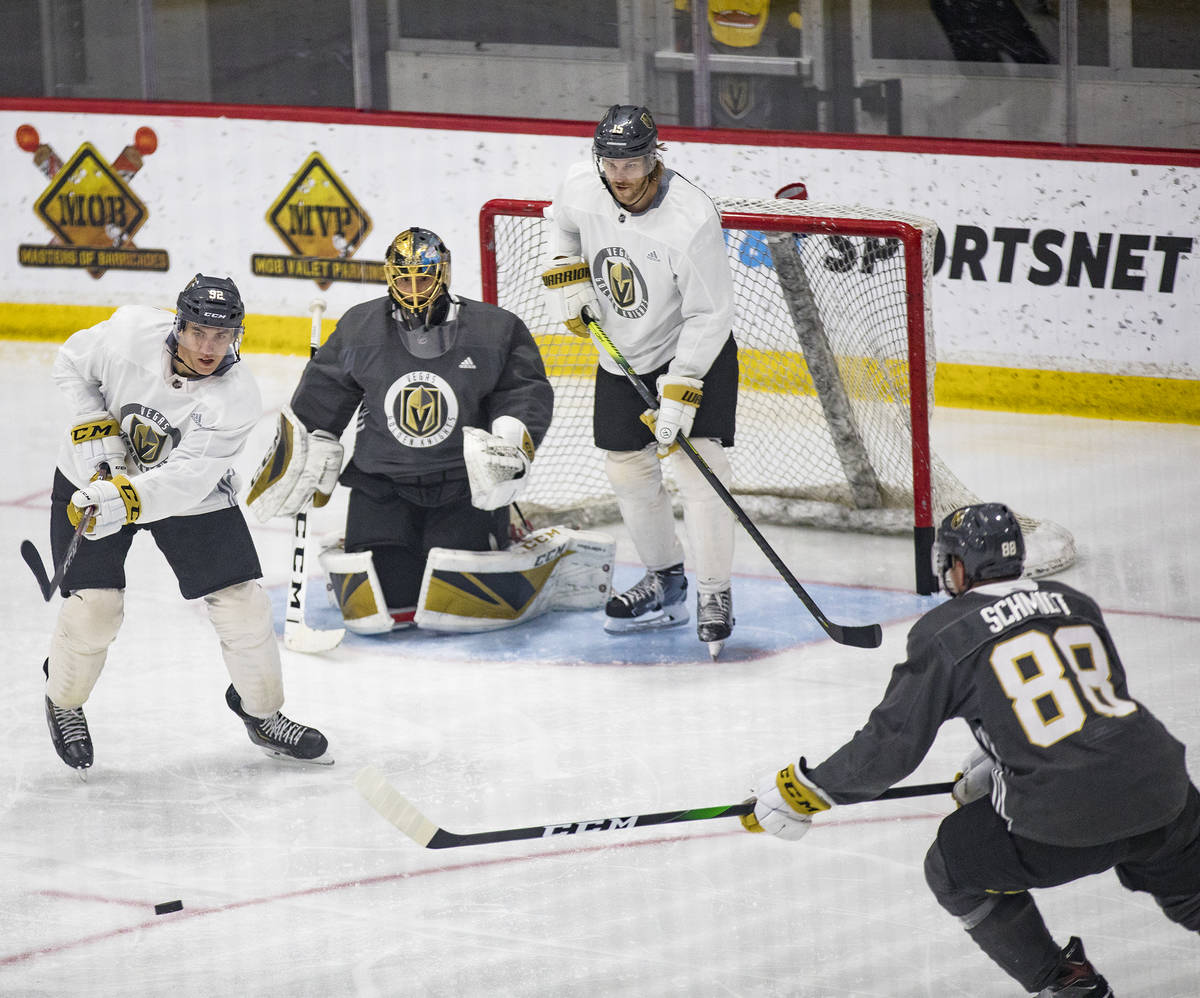 Golden Knights' Tomas Nosek (92) tries to steal the puck from Nate Schmidt (88) as players Jon ...