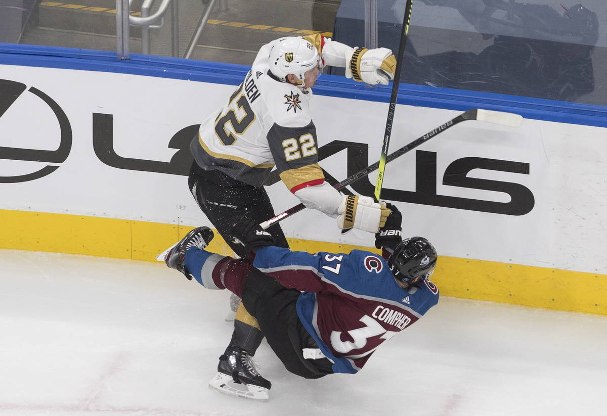 Colorado Avalanche's J.T. Compher (37) is checked by Vegas Golden Knights' Nick Holden (22) dur ...