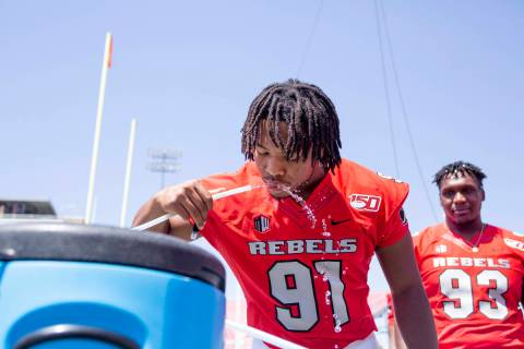 UNLV's defensive line Nate Neal (91) hydrates during the team's photo day at Sam Boyd Stadium i ...