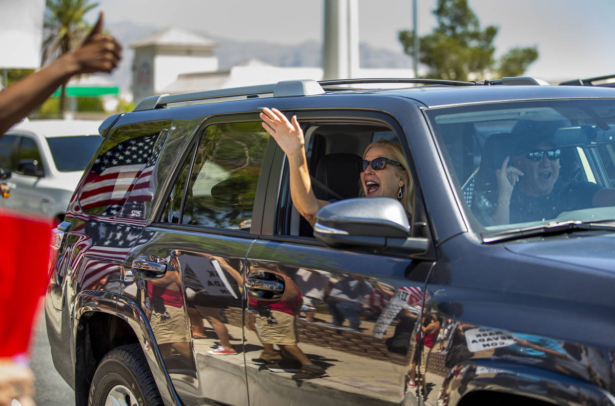 A driver and passenger show their support as they pass by a No Mask Nevada rally to oppose the ...