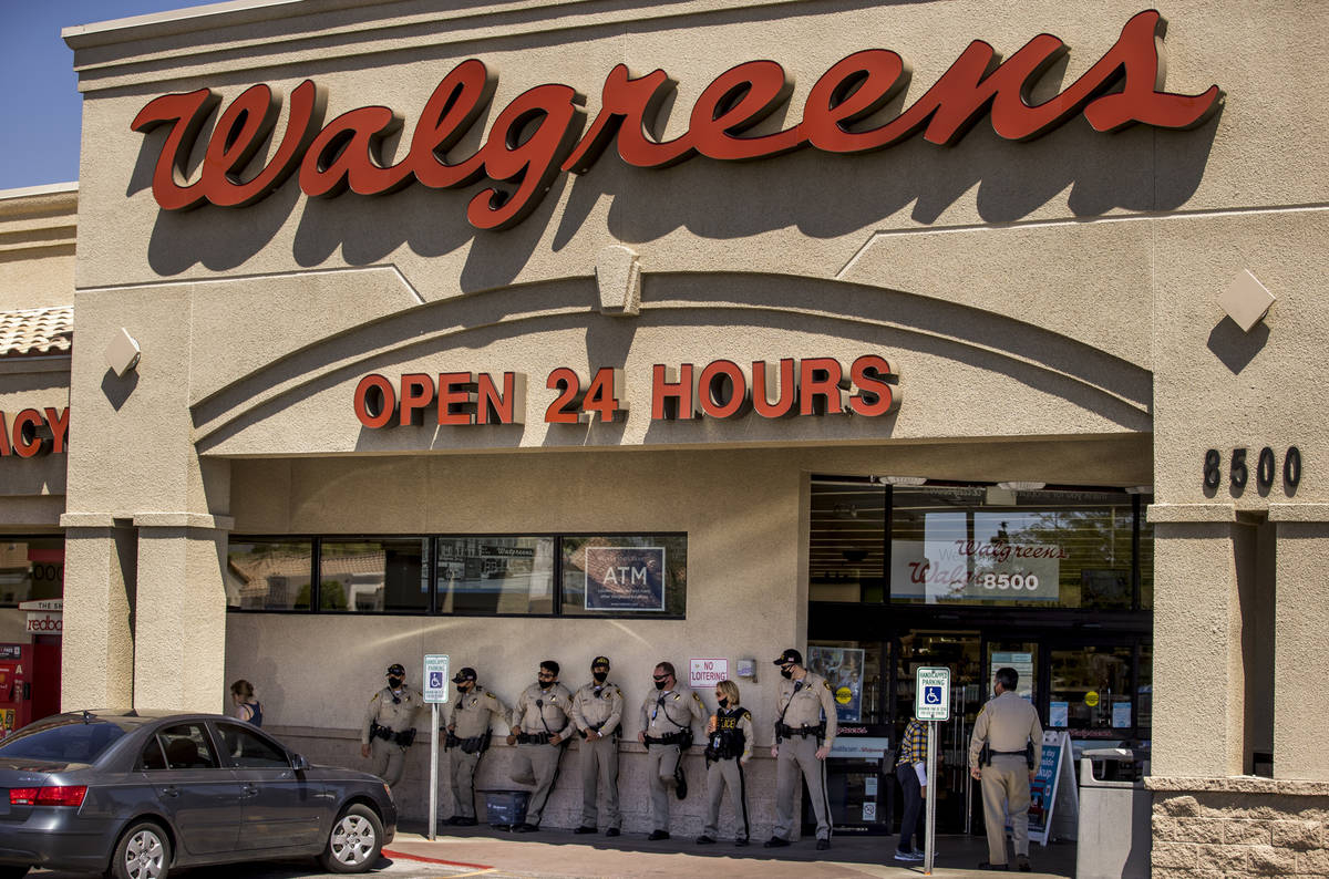 Las Vegas police officers keep cool at Walgreens while monitoring a No Mask Nevada rally to opp ...