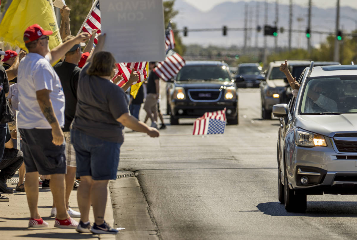 "A driver gives the "" thumbs up "" sign to supporters during a No Mask Nevada rally to ..."