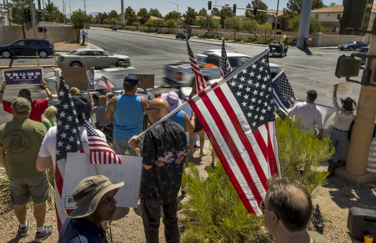 Supporters chat as traffic streams by during a No Mask Nevada rally to oppose the face mask man ...