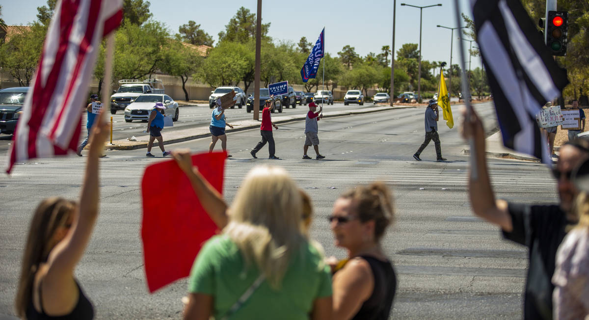 Supporters carrying flags and signs make another cross of traffic during the No Mask Nevada ral ...