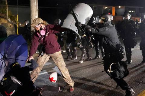 A Portland police officer shoves a protester as police try to disperse the crowd in front of th ...