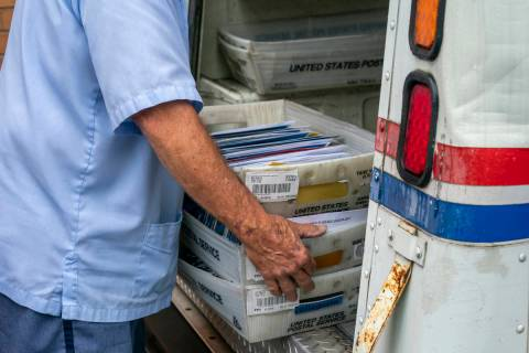 FILE - In this July 31, 2020, file photo, letter carriers load mail trucks for deliveries at a ...