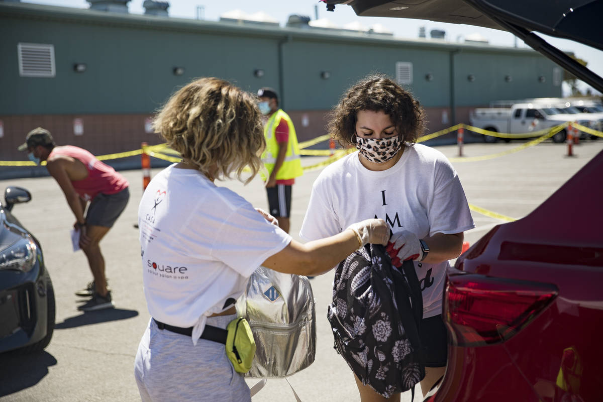Volunteers Theresa Broussard, left, hands backpacks to Vicky Murillo, right, to put in a car of ...