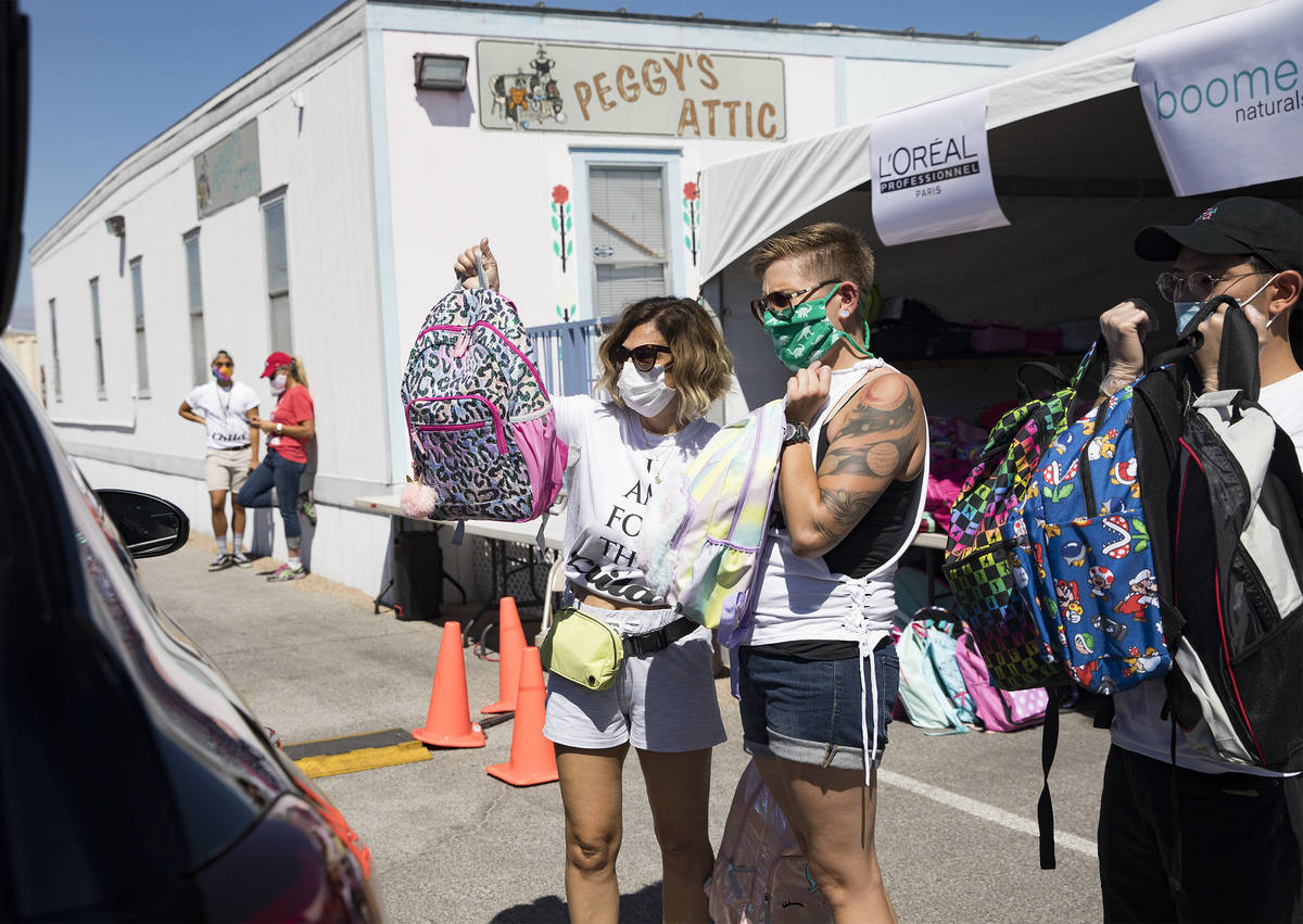 Volunteers Theresa Broussard, left, and Alexis Von Schlieder, center, and Dillon Mones, right, ...