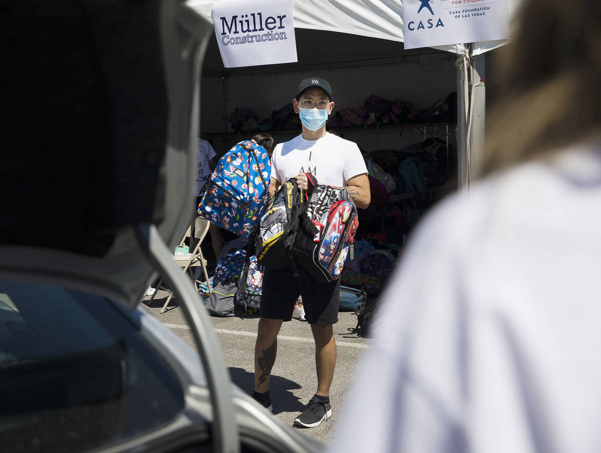 Volunteer Dillon Mones shows backpacks to foster children in a car at a back-to-school drive ma ...
