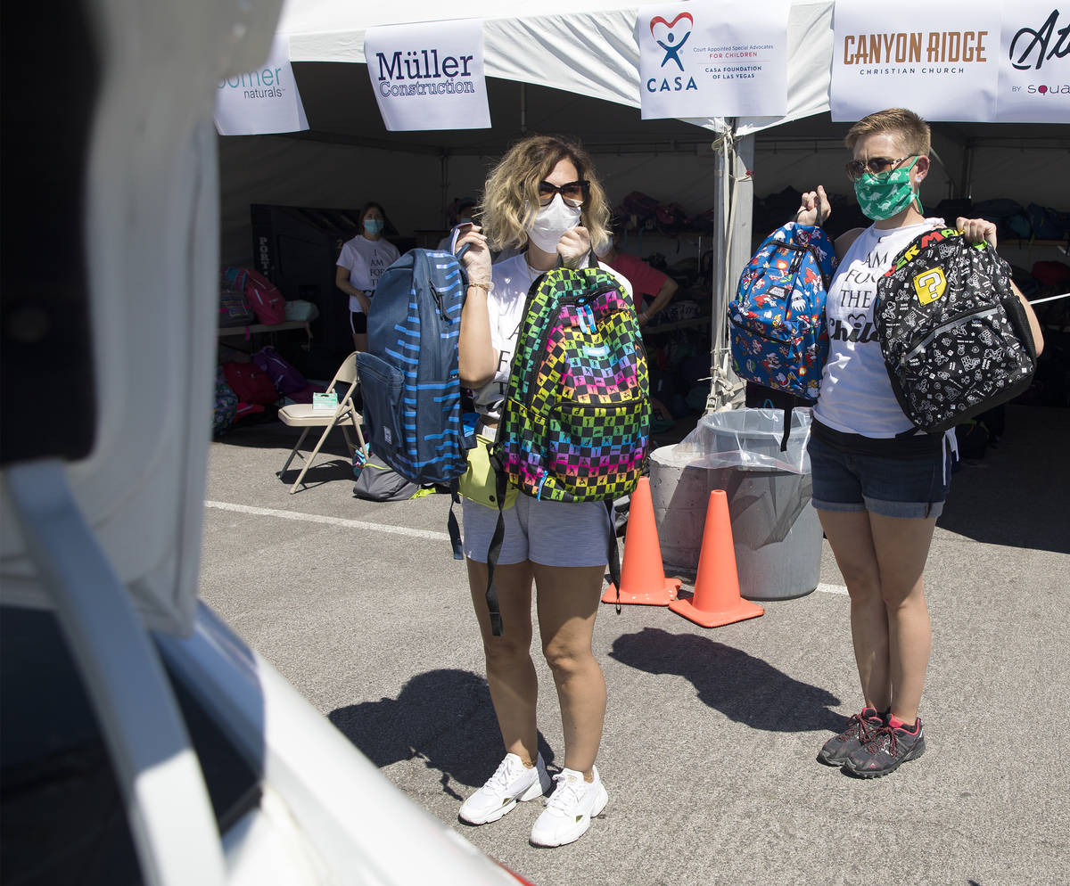 Volunteers Theresa Broussard, left, and Alexis Von Schlieder, right, show backpacks to foster k ...