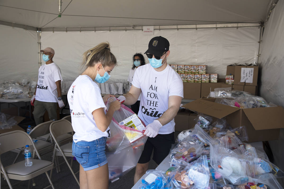 Volunteers Shally Matlovick, left, and Max Guy, right, gather supplies together to give away at ...